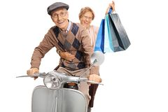 Elderly man and woman with shopping bags riding a vintage scooter stock photos