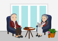 An elderly man and woman sitting in living room. An elderly man and woman sitting on a navy blue sofa in living room with coffee and cookies on the side table Royalty Free Stock Photos