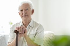 Elderly man with wooden walking stick in the nursing house. Concept photo royalty free stock image