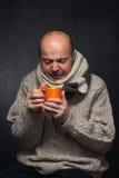 Elderly man in a woolen scarf drinking cold medicine. Stock Photo