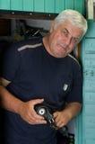 An elderly man working. An elderly man with a drill Stock Photography