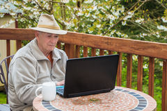Elderly Man Working on Laptop Computer. Serious senior male sitting at a table out on backyard deck working on a laptop computer Royalty Free Stock Photos