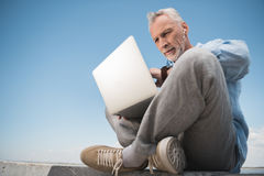 Elderly man working on laptop and listening music in earpods outdoors Stock Photo