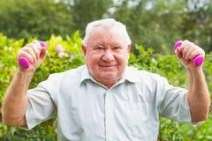 Elderly man workout. Elderly man doing fitness exercises with dumbbells in the park stock photo
