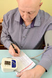 The elderly man writes down indicators in the diary of control of arterial pressure.  stock photos