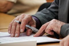An elderly man writes a pen in the questionnaire. Old age and learning. Unemployment and retirement royalty free stock photography