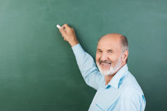 Elderly man writing on a blank chalkboard. Elderly man with a friendly smile writing on a blank chalkboard during a business presentation or while teaching class Stock Photography