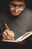 An elderly man writing in a notebook Stock Photography