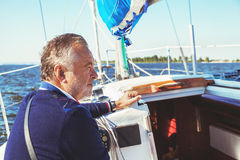 Elderly man on yacht at sea. Elderly solid man sitting on a yacht while sailing in open water stock images