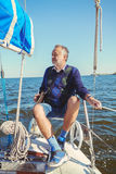 Elderly man on yacht at sea. Elderly solid man sitting on a yacht while sailing in open water stock photos