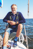 Elderly man on yacht at sea. Elderly solid man sitting on a yacht while sailing in open water royalty free stock photo
