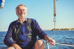 Elderly man on yacht at sea. Elderly solid man sitting on a yacht while sailing in open water stock photography