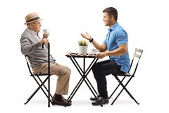 Elderly man and young man sitting at a table having a conversation and drinking coffee royalty free stock photo