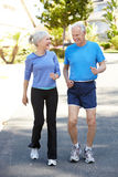 Elderly man and younger woman jogging Royalty Free Stock Image