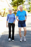 Elderly man and younger woman jogging Stock Images
