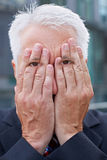 Elderly manager with eyes on hands. Covering his face Royalty Free Stock Image