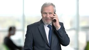 Elderly manager talking on cell phone. Senior man in formal wear using his smartphone on office background. Businessman talking on phone with partners stock video footage