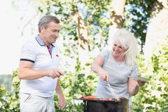 Elderly marriage grilling meat together. Royalty Free Stock Photo
