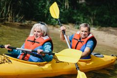 Elderly marriage rowing in the kayak Royalty Free Stock Images