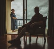 An elderly married couple at home, the husband sits indoors on the armchair, the wife stands on the balcony and looks at stock photo