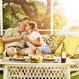 Elderly married couple kissing. Photo of elderly married couple kissing on patio with wine glasses royalty free stock images