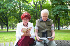 Happy elderly couple reading. Attractive elderly couple reading  outdoors Royalty Free Stock Photos