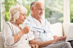Elderly married couple using laptop Stock Photos