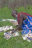 Elderly Massai woman selling handmade beaded jewelry on a blanket in Tanzania, Africa. Stock Images