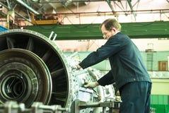 Elderly mechanic assembles aviation engine royalty free stock photo