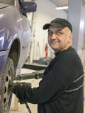 Elderly mechanic fixing old car. Elderly reluctant mechanic fixing old blue car royalty free stock images