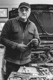 Elderly mechanic in front of car b/w. Elderly mechanic fixing a car royalty free stock image
