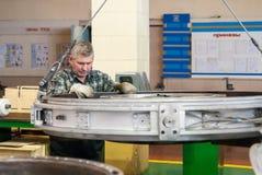 Elderly mechanic transports detail of engine Royalty Free Stock Photos