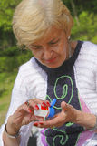 Elderly medication. Senior woman taking pills from a bottle in a park Royalty Free Stock Photos