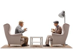 Elderly men with cups sitting in armchairs Royalty Free Stock Photos