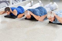 Elderly men doing back exercises. In fitness center royalty free stock photography