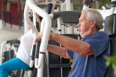 Elderly man doing press push weight exercise. Elderly men doing press push weight exercise. Male person doing hard workout on fitness machine at gym. Healthy royalty free stock photo