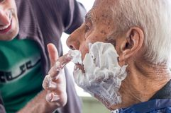 Old man getting his beard shaved by young skilled man at home. Elderly men getting his beard shaved by young skilled men at home. Man applying shaving foam to royalty free stock photography