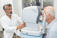 Elderly man with glaucoma at optician for optical examination Stock Photography