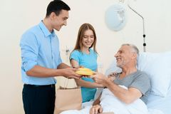 An elderly man lies in a hospital room on a bed. He is seen by a man with a woman. A woman is standing next to him. An elderly men lies in a hospital room on a Stock Image