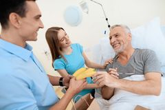 An elderly man lies in a hospital room on a bed. He is seen by a man with a woman. A woman is standing next to him. An elderly men lies in a hospital room on a Stock Photos