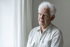 Elderly man looking away and thinking stock photo