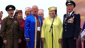 Elderly men in military uniform and women in color costume sing a song stock footage
