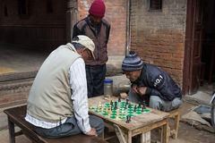 Elderly men playing chess in Bhaktapur, Nepal. Bhaktapur, Nepal - December 5, 2014: Elderly men playing chess in the streets royalty free stock image