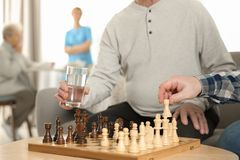 Elderly men playing chess at nursing home. Assisting senior people royalty free stock images