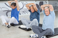 Elderly men stretching in fitness Stock Photos