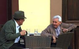 Elderly men talking in the street cafe in Ronda stock images
