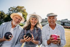 Elderly men and a woman sitting outdoors holding boules royalty free stock photo