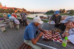 Elderly mens play chess on the embankment of Vistula. KRAKOW, POLAND - FEB 8, 2016: Unidentified elderly mens play chess on the embankment of Vistula. There are royalty free stock photos