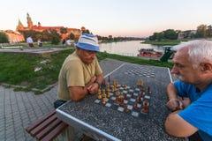 Elderly mens play chess on the embankment of Vistula. KRAKOW, POLAND - FEB 8, 2016: Unidentified elderly mens play chess on the embankment of Vistula. There are stock images