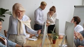 Elderly mentors helping interns with corporate program moving camera slider stock video